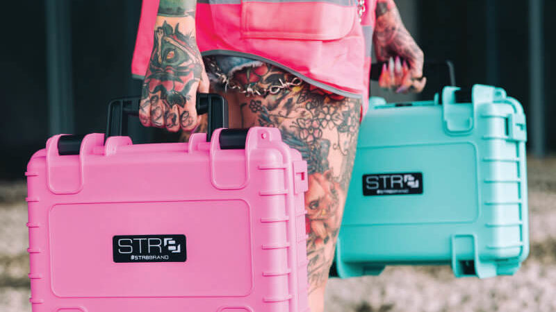 Tattoo model wearing ripped jean shorts with chain and pink vest carrying a 17 Inch STR8 Case With 3 Layer Pre Cut Foam in Electric Pink and STR8 Teal
