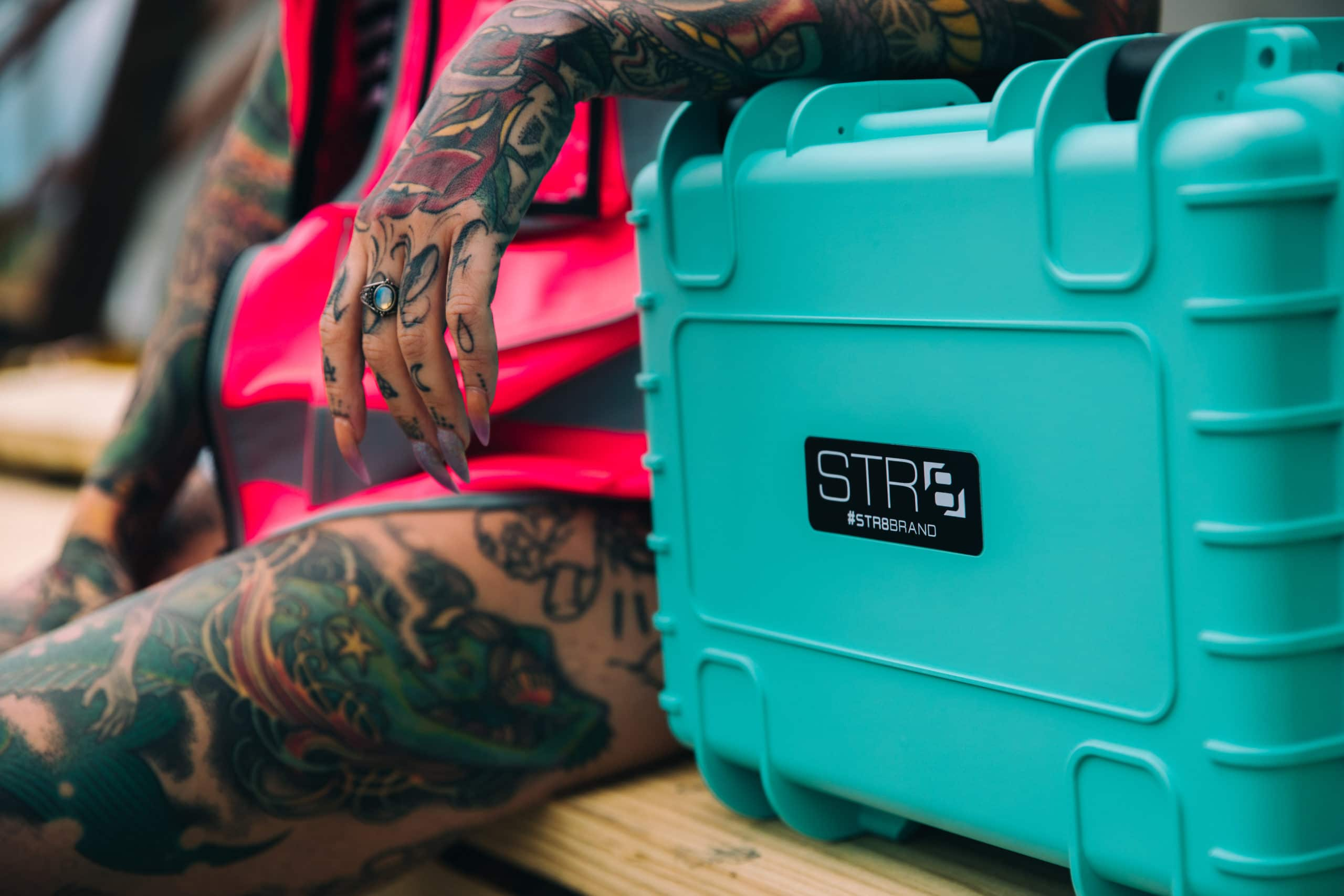 Female tattoo model sitting on ledge wearing a pink vest and opal ring with nail art against a blurred background leaning on a 17 Inch STR8 Case With 3 Layer Pre Cut Foam in STR8 Teal